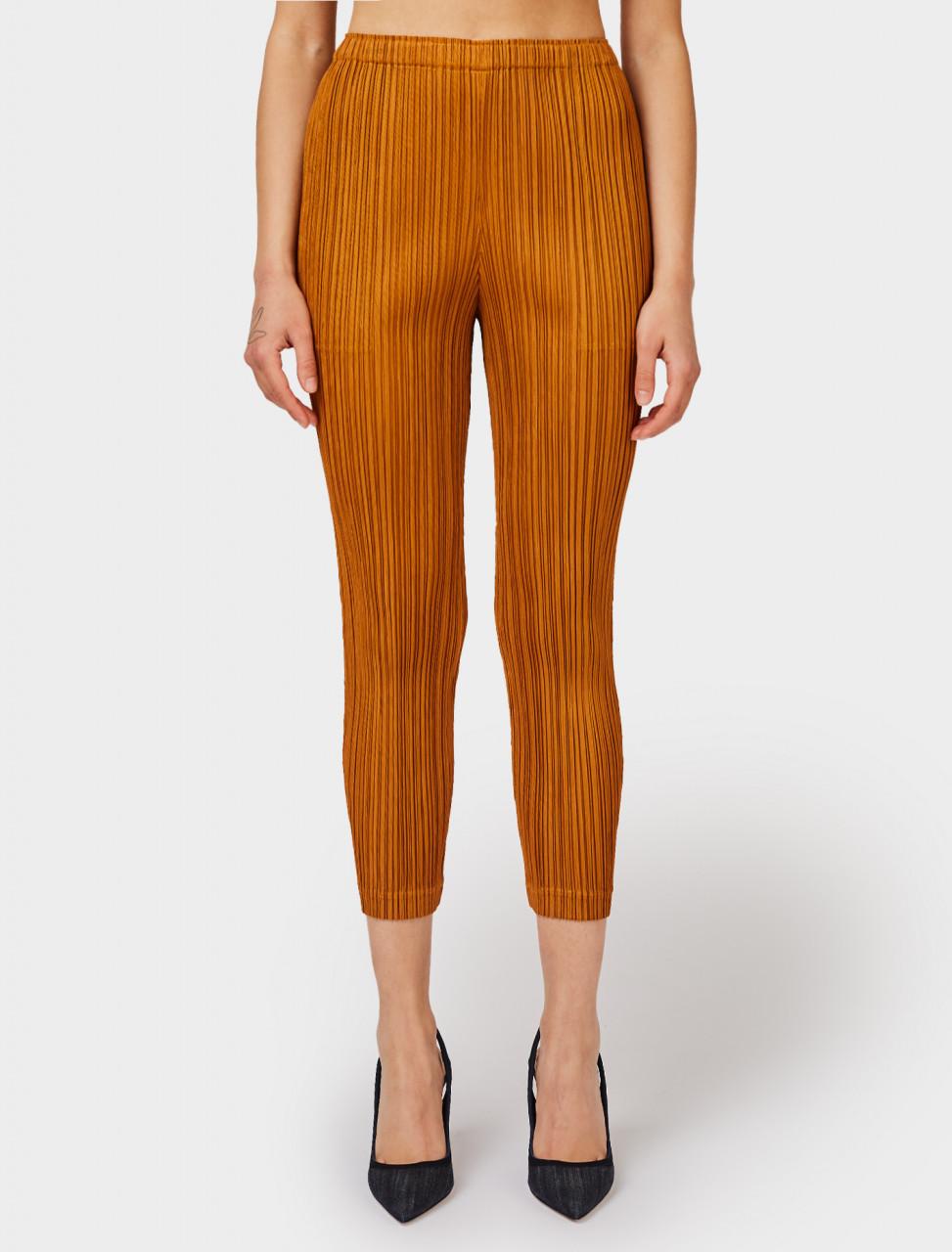 Front view of Pleats Please Issey Miyake Slim Leg Pleated Trousers in Orange Brown